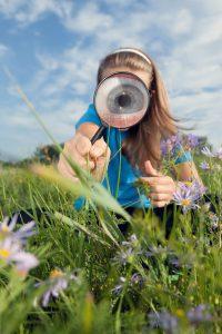 Et barn holder et forstørrelsesglas, hvor igennem man kan se et stort øje, der kikker på græsses og lilla blomster.