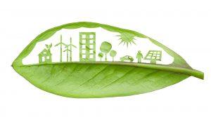 En grøn by skåret ud i et blad, på baggrund af hvid. Et hus med blade i toppen, vindmøller der ligner trekløvere, et højhus, tre træer, en bil, sol, person og solcelle