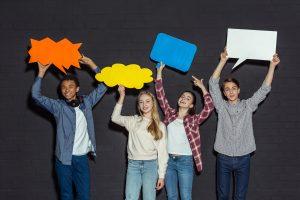 En gruppe teenagere holder blande tale bobler over deres hoveder på en mørk baggrund.